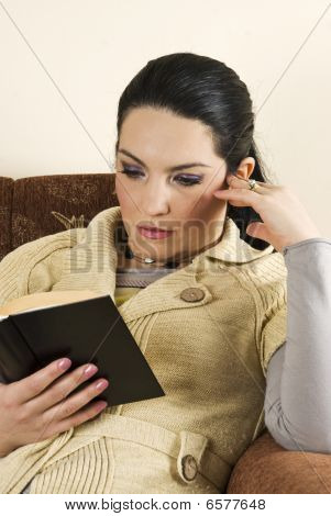 Woman In Sofa Reading A Book