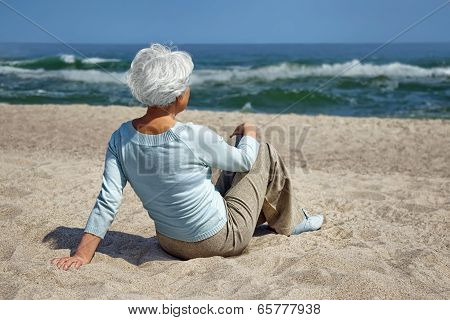 Elderly Woman Sitting In The Sand On The Beach And Looks Into The Distance The Sea Horizon