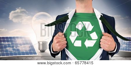 Businessman opening shirt in superhero style against light bulb and solar panels on floorboards in the sky