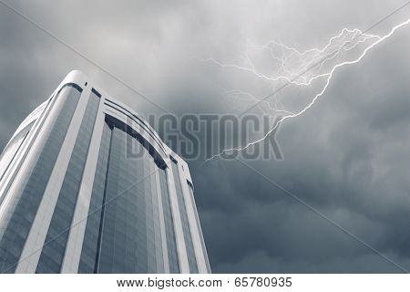 Bottom image of skyscraper with thunder lightning in sky
