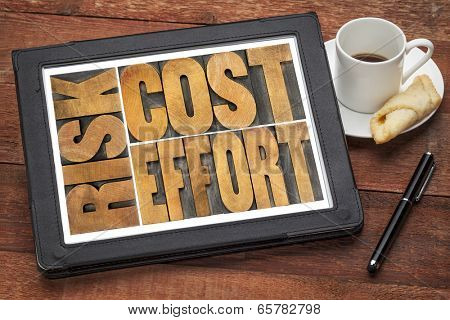 cost, effort, risk - business concept - a word abstract  in vintage wood letterpress printing blocks on a digital tablet with cup of coffee