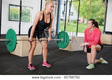 woman lifts weights with personal trainer