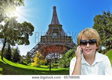 The beautiful fair-haired boy cheerfully stirs with friends by the mobile phone. Background - the Eiffel Tower. The picture is made a lens the Fisheye