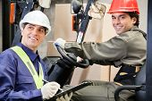 stock photo of forklift driver  - Portrait of young forklift driver with supervisor writing notes at warehouse - JPG