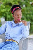 pic of jamaican  - Stock image of a young Jamaican woman sitting and glancing away from the camera - JPG