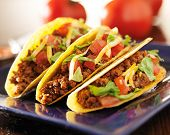 stock photo of shredded cheese  - three beef tacos with cheese - JPG