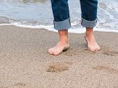 picture of wet pants  - Detail of male feet at the beach with a wave of foaming water - JPG