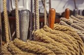 stock photo of pegging  - Rows of aged natural fiber ropes on metal pegs on ancient sailing vessel board - JPG