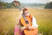 stock photo of hippy  - Pretty country hippie girl playing guitar on grass - JPG