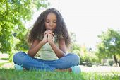 stock photo of evangelism  - Young girl praying in the park on a sunny day - JPG