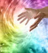 stock photo of cosmic  - Outstretched healing hands on vivid rainbow vortex swirling energy background - JPG