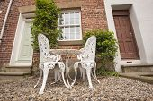image of english ivy  - Set of white garden table and chairs on patio outside rural house - JPG