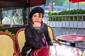 stock photo of 13 year old  - 13 year old teenager in a French beret and scarf sitting at a table Parisian cafe on the Champs Elysees - JPG