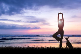 foto of breathing exercise  - Silhouette of young woman practising yoga being one perfect harmony with nature facing ocean on sunset with her dog - JPG