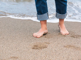 pic of wet pants  - Detail of male feet at the beach with a wave of foaming water - JPG