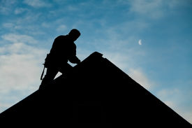 image of moon silhouette  - Contractor in Silhouette working on a Roof Top with blue Sky in Background - JPG