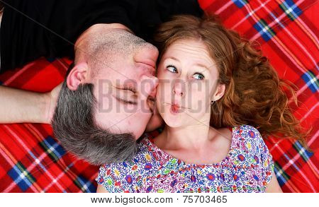 Girlfriend lying on a rug pulls a funny face