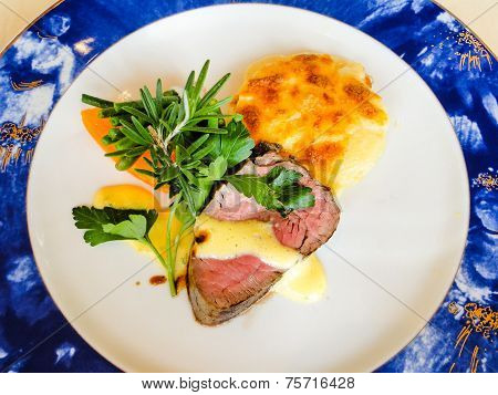 Beef Tenderloin With Bernaise Sauce, Potatoes Au Gratin, Carrots. Garnished With Rosemary And Parsle