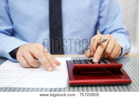 Businessman Calculating  And Checking Articles Of Agreement