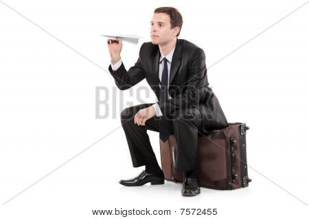 A businessman sitting on a luggage and holding a paper toy plane