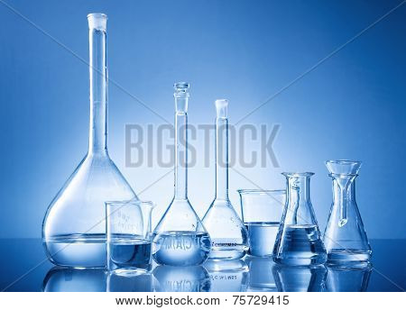 Laboratory equipment bottles flasks on blue background