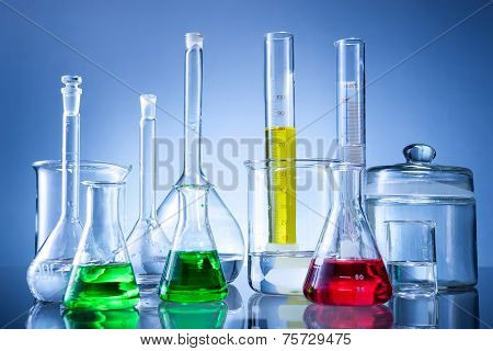 Laboratory equipment bottles flasks with color liquid on blue background