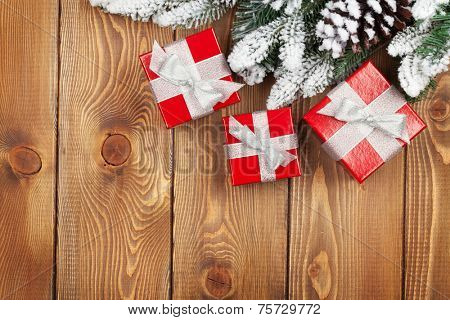 Christmas fir tree with snow and red gift boxes on rustic wooden board with copy space