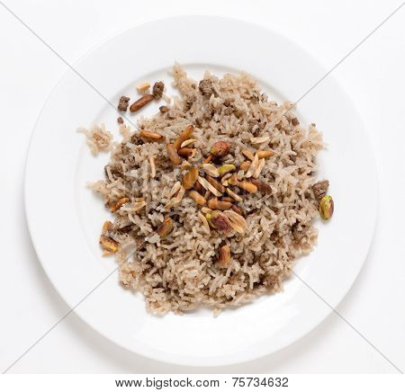 Lebanese spiced rice with minced beef and garnished with freshly toasted nuts on a plate viewed from above