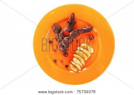grilled beef meat with berries fried potatoes and cherry under sweet honey sauce on orange plate isolated over white background high resolution hidef