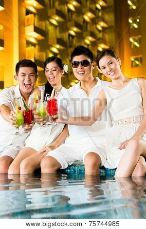 Two young and handsome Asian Chinese couples or friends drinking cocktails in a luxurious and fancy hotel pool bar