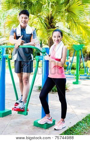 Asian Chinese man and woman training fitness on public cross trainer in outdoor gym