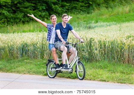 Man and woman, a couple,  riding together tandem bike on country lane