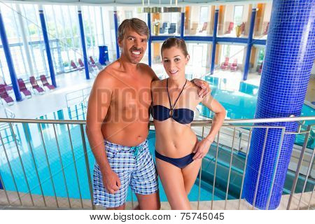 Man and woman standing in wellness thermal spa with columns and dome, the pool in the background