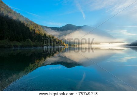 morning dust at idyllic lake plansee in autumn with mirroring mountains