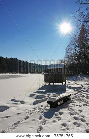 Wooden Fishing Hut And Snow Covered Lake