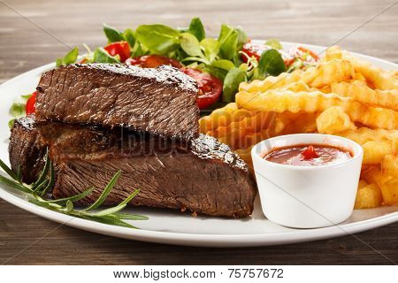 Beefsteaks, French fries and vegetables