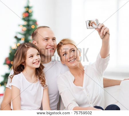 family, holidays, technology and people - smiling mother, father and little girl making selfie with camera over living room and christmas tree background