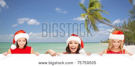 christmas, x-mas, people, advertisement and sale concept - happy women in santa helper hat with blank white board over tropical beach background