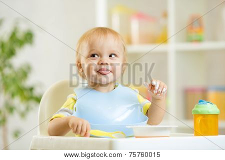 smiling baby kid boy eating itself with spoon