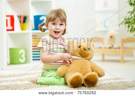 child girl playing doctor with plush toy at home