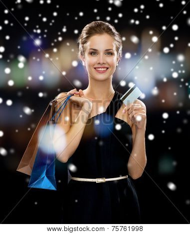 people, sale, banking, money and holidays concept - smiling woman in dress with shopping bags and credit card over snow and night lights background