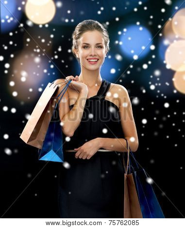 luxury, holydays, people and sale concept - smiling woman with shopping bags over snow and night lights background