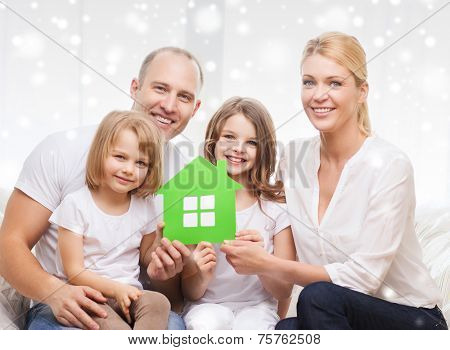 real estate, family, people and home concept - smiling parents with two little girls holding green paper house