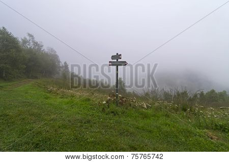 Pointer To A Hiking Trail In The Mountains Covered With Dense Fog.