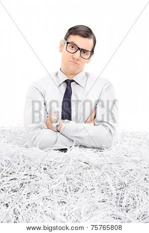 Sad man in a pile of shredded paper isolated on white background