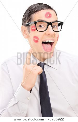 Happy guy showing the lipstick kiss marks on his face isolated on white background