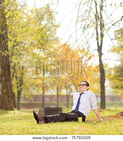 Businessman relaxing seated on the grass in park shot with tilt and shift lens