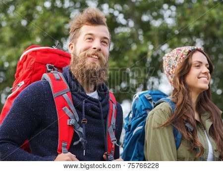 adventure, travel, tourism, hike and people concept - group of smiling friends walking with backpacks
