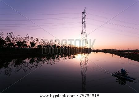 high voltage transmission tower and landscape during sunset