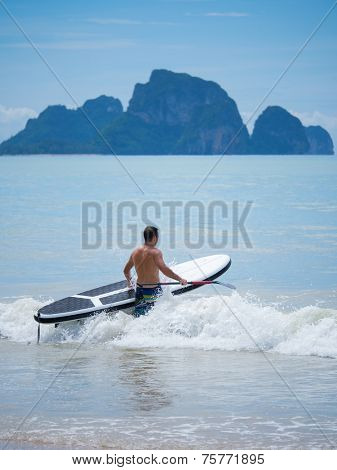 Young man stand up paddle boarding in Thailand on a stormy day